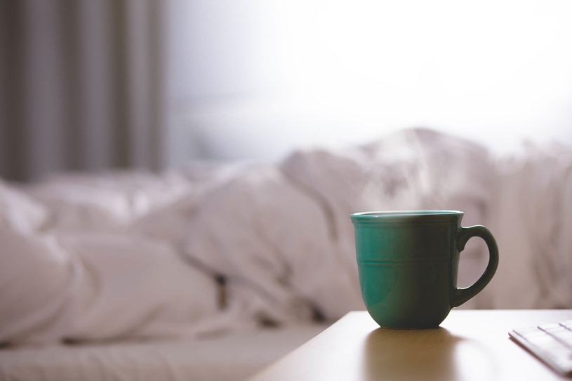 hot coffee mug next to bed